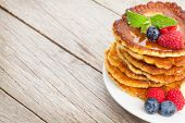 Pancakes with raspberry, blueberry, mint and honey syrup. On wooden table with copy space