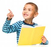 Cute little boy is reading a book while pointing to the left using his index finger, isolated over white