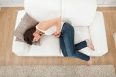 Woman Suffering From Stomachache On Sofa