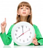 Little girl is holding big clock while pointing up with her index finger, isolated over white