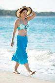 Young Woman Wearing Sunhat Walking On Beach
