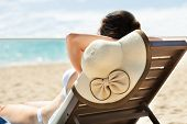 Woman With Sunhat Relaxing On Deck Chair