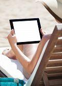 Woman Using Digital Tablet On Beach Chair