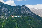 flying turboprop airplane against apls mountains background