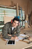 Portrait of confident carpenter working on blueprint while wearing ear protectors at table in workshop