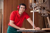 Portrait of confident male carpenter using bandsaw to cut wood in workshop