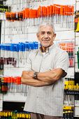 Portrait of confident senior male customer with arms crossed standing in hardware shop