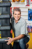 Portrait of smiling mature man lifting stacked toolboxes in hardware shop