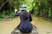 Woman rowing boat in the forest, Vietnam