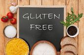 foto of wheat-free  - Gluten free sign handwritten on a chalk board surrounded by ingrediients - JPG