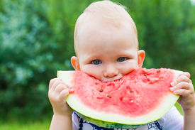 stock photo of eat grass  - cute little girl eating watermelon on the grass in summertime - JPG