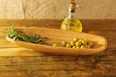 Green olives and branch in oblong bowl with oil can on rustic wooden table, on burlap background