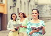 tourism, travel, leisure and holidays concept - smiling teenage girls with city guide, map and camera outdoors