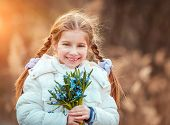 happy little girl smiling and holding a bouquet of blue snowdrops