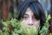 Closeup portrait of black-haired teen girl, hidden in the greenery of the garden.