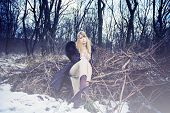 blonde woman in coat and long wool dress in hippie style apperel sit on branches in the forest, cold winter day