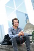 Urban man on smart phone wearing headphones listening to music or having video chat conversation sitting outside using app on 4g smartphones. Casual young urban professional male in Hong Kong Central.