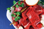 fresh uncooked beef meat slices over white bowls ready to prepare with red peppers and greenery serving on blue table with cutlery