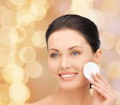 beauty, people and health concept - beautiful smiling woman cleaning face skin with cotton pad over beige lights backgroundd