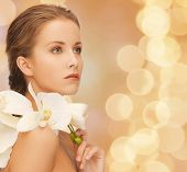 beauty, people and health concept - beautiful young woman with orchid flowers and bare shoulders over beige lights background