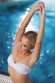 people, beauty, spa, healthy lifestyle and relaxation concept - beautiful young woman wearing bikini swimsuit sitting with raised hands in jacuzzi at poolside