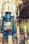 Old Blue Kerosene Lamp Hangs On Wooden Outdoor Fence