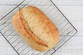 High angle closeup of a fresh baked loaf of bread on a cooling rack. Horizontal format on a rustic whitewashed kitchen table, with copy space.