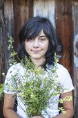 Black-haired teen girl with a bouquet of greenery outdoors.
