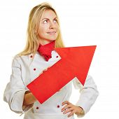 Smiling female chef cook holding a red arrow pointing up