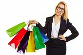 Happy businesswoman with glasses carrying many shopping bags in different colors