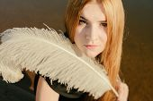 stock photo of gothic hair  - unusual gothic girl with long red hair and white feather - JPG