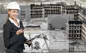 Beautiful businesswoman in helmet holding paper holder and portable radio. Construction site as back