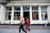 NEW YORK CITY - TUESDAY, DEC. 30, 2014: Pedestrians walk past a Tommy Hilfiger store. Tommy Hilfiger is an American fashion, apparel, design, fragrance retail company