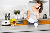 Young cheerful woman talking on the phone in kitchen
