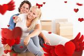 Woman sitting with her fiance giving keys against love heart pattern