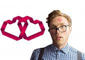 Geeky hipster covered in kisses against linking hearts