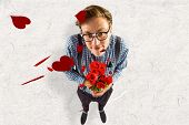 Geeky hipster holding a bunch of roses against parchment