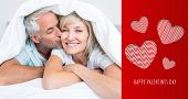 Closeup of mature man kissing womans cheek in bed against cute valentines message