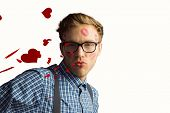 Geeky hipster covered in kisses against red love hearts