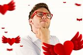 Young geeky businessman with hand on chin against hearts