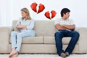 A couple sit at the two ends of the couch with their arms folded looking away against broken hearts