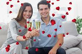 Portrait of lovers toasting their flutes of champagne against valentines heart design