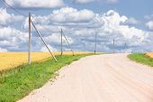 Rural Gravel Road With Fields And Wire Lines