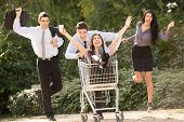 stock photo of trolley  - Group of young business people elegantly dressed in a park with a shopping trolley which pushed their colleague in euphoric motion - JPG
