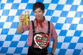 Young man dressed in leather pants (lederhose) holding an Oktoberfest beer stein into camera.
