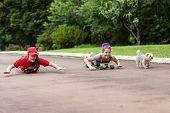 foto of driveway  - Girls having fun skateboarding home driveway with dogs - JPG
