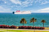stock photo of passenger ship  - Passenger ship sails along the promenade with palm trees against the blue sky and beautiful clouds - JPG