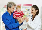 Cheerful female pharmacist chemist showing tablet vitamins to father man with little baby child girl in pharmacy drugstore