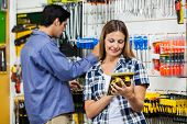 Mid adult female customer looking at packed product with man in background at hardware store