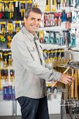 Portrait of happy mature man buying hammer in hardware store
